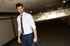 Handsome businessman walking in underpass. Handsome young businessman walking in underpass, looking away Stock Photography