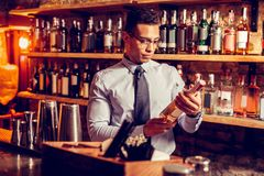 Handsome businessman wearing glasses holding bottle of whisky royalty free stock photos