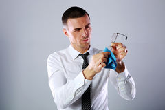 Handsome businessman wiping eyeglasses Stock Photo