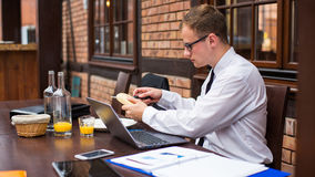 Handsome businessman work at the laptop in restaurant. Royalty Free Stock Photography