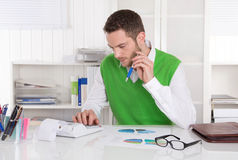 Handsome businessman working at desk at office. Stock Photo