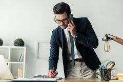 Handsome businessman working. Handsome businessman in eyeglasses is taking notes while talking on the mobile phone in the office Royalty Free Stock Image