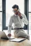 Handsome businessman working. Handsome businessman in eyeglasses is talking on the mobile phone and using a laptop while working in the office Royalty Free Stock Photo