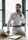 Handsome businessman working. Handsome businessman in eyeglasses is talking on the mobile phone and using a laptop while working in the office Royalty Free Stock Photos