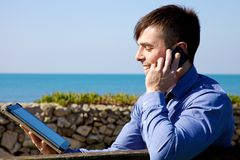 Handsome businessman working in front of the ocean Stock Photo