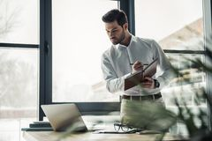 Handsome businessman working. Handsome businessman is making notes while working with a laptop in the office Royalty Free Stock Image