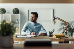 Handsome businessman working. Handsome pensive businessman is making notes and looking away while working in the office Stock Photos