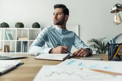 Handsome businessman working. Handsome pensive businessman is making notes and looking away while working in the office Royalty Free Stock Photography