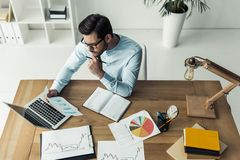 Handsome businessman working. High angle view of handsome businessman in eyeglasses is examining documents while working with the laptop in the office Royalty Free Stock Photo