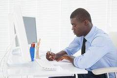 Handsome businessman working at his desk Stock Image