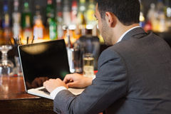 Handsome businessman working on his laptop while having a drink Stock Photography