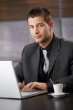 Handsome businessman working on laptop Stock Photos