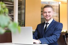 Handsome businessman working with laptop in  cafe. Handsome businessman working with laptop in street cafe Stock Photography