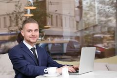 Handsome businessman working with laptop in  cafe. Handsome businessman working with laptop in street cafe Stock Images