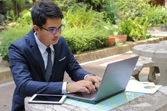 Handsome businessman working with laptop computer outdoors in park Royalty Free Stock Photo