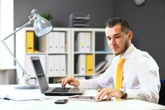 Handsome businessman working with laptop Stock Images