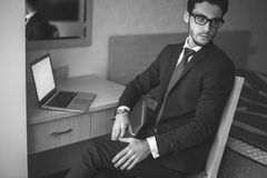 Handsome businessman working with laptop in office. Finance market analyst in eyeglasses working at sunny office on laptop while sitting at chair royalty free stock photo