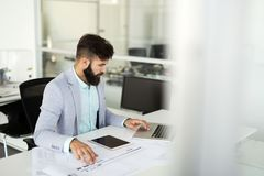 Handsome businessman working on laptop in office. Handsome businessman working on laptop in modern office stock photography