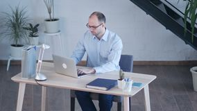 Handsome businessman working with laptop in office stock footage