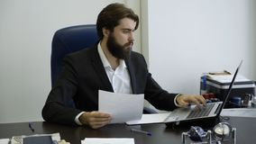 Handsome businessman working with laptop in office. Young businessman with a beard working at the computer in the office stock image