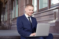 Handsome businessman working with laptop while sitting. On stairs outdoors Stock Photo