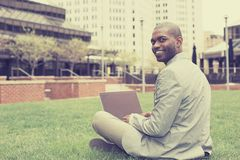Handsome businessman working with laptop sitting outdoors. Handsome young businessman working with laptop looking at camera sitting outdoors. Instagram filter Royalty Free Stock Photos