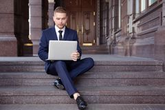 Handsome businessman working with laptop while sitting on stairs. Outdoors Stock Photo