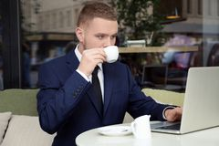 Handsome businessman working with laptop in  cafe. Handsome businessman working with laptop in street cafe Royalty Free Stock Photos