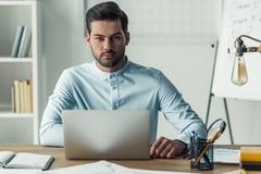 Handsome businessman working. Handsome businessman is looking at camera while working with the laptop in the office Stock Images