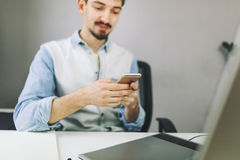 Handsome businessman working in office using mobile phone Stock Photos