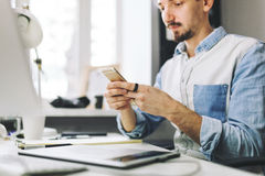 Handsome businessman working in office using mobile phone Royalty Free Stock Photo