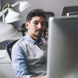 Handsome businessman working in office using mobile phone Royalty Free Stock Image