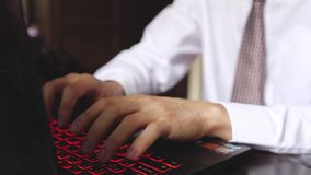 Handsome businessman working on an office. Young man typing on a laptop. Close up of male hands. 3840x2160. Handsome businessman working on an office. Focused stock video footage