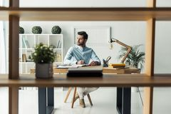 Handsome businessman working. Handsome pensive businessman is making notes and looking away while working in the office, view through the shelf Royalty Free Stock Image