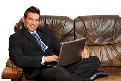 Handsome businessman works on the computer. Handsome businessman in suit sitting on sofa and works on the computer Stock Photo