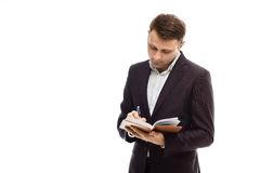 Handsome businessman writing in a diary. Handsome businessman in suit writing in a diary isolated on white Royalty Free Stock Photo