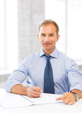 Handsome businessman writing in notebook Royalty Free Stock Photos