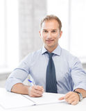 Handsome businessman writing in notebook Stock Photography