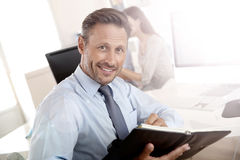 Handsome businessman writing notes in agenda Stock Photography