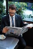 The handsome businessmen the reading the newspaper in lunchtime. Portrait of young brunette hair businessman sitting in a coffee shop reading a newspaper looking royalty free stock photography