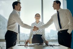 Handsome businessmen shaking hands having negotiated a deal. Consensus is reached. Handsome young businessmen shaking hands having negotiated a deal while their Royalty Free Stock Photography