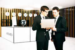 Handsome businessmen using laptop together. On modern reception background. Teamwork concept. 3D Rendering Royalty Free Stock Photography