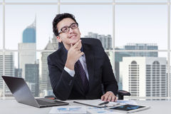 Handsome businessperson daydreaming in office. Young caucasian businessman smiling happy while daydreaming in the office Stock Images
