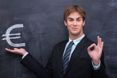 Handsome bussinesman hold the euro symbol. Male in bussines suit showing OK gesture Royalty Free Stock Photos