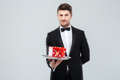 Handsome butler in tuxedo with bowtie gift box on tray royalty free stock photos