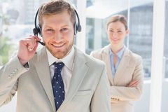 Handsome call centre agent with colleague behind him Stock Photos