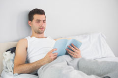 Handsome calm man reading book in his bed. In bright bedroom Royalty Free Stock Photography