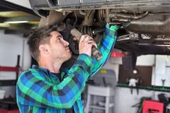 Handsome car mechanic checking suspension system of a lifted car at repair service station. Handsome car mechanic checking suspension system of a lifted car at royalty free stock images