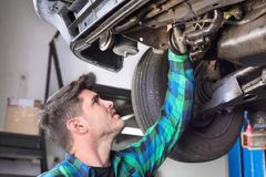 Handsome car mechanic checking suspension system of a lifted car at repair service station. Handsome car mechanic checking suspension system of a lifted car at stock photography