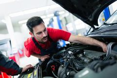 Car mechanic working at automotive service center. Handsome car mechanic working at automotive service center stock image